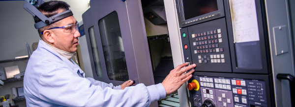 Machinist programing a CNC machine at Altair USA