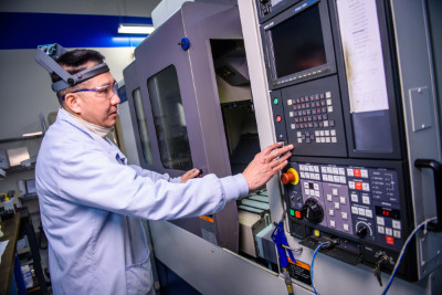 CNC machinists programming a vertical mill at Altair Technologies Inc. USA